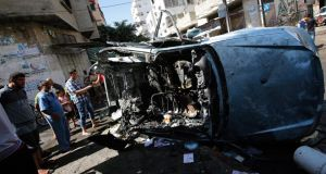 Palestinians inspect a destroyed car after Israeli air strikes in Gaza City yesterday. Photograph: EPA/Mohammed Saber