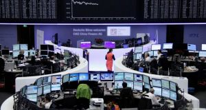 Traders are pictured at their desks in front of the DAX board at the Frankfurt stock exchange. Photograph: Reuters