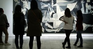 Museum visitors take in Picasso's Guernica.