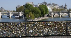 Lovers are asked to take a photo of themselves rather than leave a lock on the Pont des Arts in Paris. Photograph: Getty