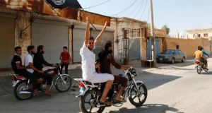 A resident of Tabqa city touring the streets on a motorcycle waves an Islamist flag in celebration after Islamic State militants took over Tabqa air base, in nearby Raqqa city August 24, 2014. Islamic State militants stormed the air base in northeast Syria on Sunday, capturing most of it from government forces after days of fighting over the strategic location, a witness and a monitoring group said. Fighting raged inside the walls of the Tabqa air base, the Syrian army's last foothold in an area otherwise controlled by IS, which has seized large areas of Syria and Iraq. REUTERS/Stringer   (SYRIA - Tags: POLITICS CIVIL UNREST CONFLICT TPX IMAGES OF THE DAY)