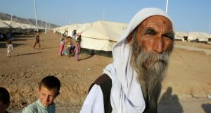 A man from the minority Yazidi sect fled violence in the Iraqi town of Sinjar. He  stands looks on in Bajed Kadal refugee camp. Photograph: Youssef Boudlal/Reuters