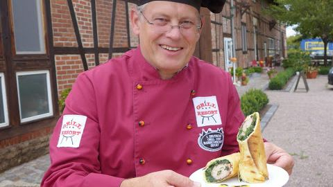 "Erfurt local and bratwurst master Andreas Bräuer, owner of Europe's oldest grill and barbecue school, with his ""Bratwurst Wrap"" creation. Photograph: Derek Scally/The Irish Times"