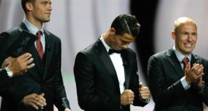 Cristiano Ronaldo (centre) reacts after being voted  Uefa's Best Player in Europe for 2013-2014 award during the Uefa Champions League draw at the Grimaldi Forum, in Monaco yesterday. Bayern Munich and Germany goalkeeper Manuel Neuer (left) and   Bayern Munich's Dutch forward Arjen Robben (right) were runners-up to the Real Madrid and  Portugal winger. Photograph: Claude Paris/AP Photo