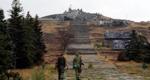Pro-Russian separatists walk towards a destroyed war memorial at Savur-Mohyla, a hill east of the city of Donetsk yesterday. Photograph: Maxim Shemetov/Reuters