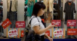 A woman passes a store in Tokyo.  Household spending fell 5.9 per cent in July from a year earlier, new figures show.