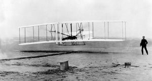 Orville Wright, at the controls of the Wright Flyer, and his brother Wilbur, watch from the ground during the plane's first flight  in   1903.  Photograph: AP Photo/File