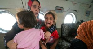 A woman and children react in a military helicopter after being evacuated by Iraqi forces from Amerli, north of Baghdad. Photograph: Stringer/Reuters