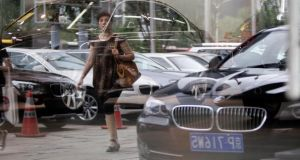 A woman is reflected on the glass wall of a BMW showroom in central Beijing. An anti-trust probe into global auto makers is being cheered on by car dealers in China, who say that companies such as Audi and Mercedes-Benz have been exploiting their dominance to boost profits. Photograph: Jason Lee/Reuters