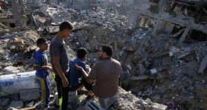 A Palestinian man and three children survey the destruction in Shejaia. Photograph: Roberto Schmidt/AFP/Getty Images
