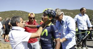 Nairo Quintana  of Movistar is helped after falling during the 11th stage of the Vuelta a Espana  race. The Colombia rider was forced to abandon the race after fracturing a shoulder blade. Photograph: Javier Lizon/EPA