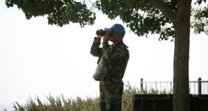 A member of the UN Disengagement Observer Force (UNDOF) looks through binoculars at the Syrian side of the Qunietra crossing from the Israeli-occupied Golan Heights. An Irish Army officer is to  become the deputy force commander of the under pressure mission. Photograph: Baz Ratner/Reuters.