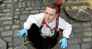 Suited and booted: Karl Whitney at a manhole entrance to the sewers – and the Poddle – on Ship Street in Dublin. Photograph: Frank Miller