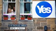 Two women wave from a window on the Royal Mile in Edinburgh, Scotland. Photograph: Jeff J Mitchell/Getty Images