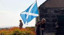 A man erects a Scottish flag  in the garden of his cottage on the Isle of Lewis in the Outer Hebrides yesterday. Photograph: Reuters