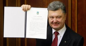 Ukraine's president Petro Poroshenko shows a signed landmark association agreement with the European Union during a session of the parliament in Kiev yesterday. Photograph: Valentyn Ogirenko/Reuters