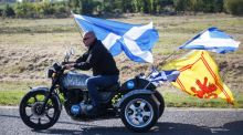 A pro-Yes motorcyclist trails the saltire flag and the lion rampant flag of Scotland while riding through the town of Kilmarnock in Scotland yesterday. Photograph: EPA/Robert Perry