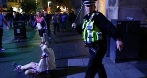 A policeman raises his baton during a demonstration at George Square in Glasgow, last night. Photograph: Cathal McNaughton/Reuters