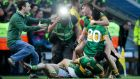 In the spotlight: Kerry players celebrateas a supporter rushes onto the pitch after the final whistle in Croke Park yesterday. Photograph: Donall Farmer/Inpho