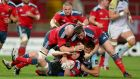 Munster's Sean Dougall is tackled by Rhys before Paul O'Connell and Denis Hurley arrive to give a helping hand. Photograph: Dan Sheridan/Inpho