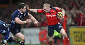 Munster's Keith Earls hands off Cian Healy of Leinster during a derby game. Photograph:  Billy Stickland/Inpho