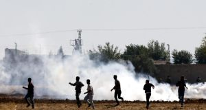 Turkish Gendarmerie use tear gas to disperse Kurdish protesters during a demonstration against Islamic State at the Syria-Turkey border near Sanliurfa today. Photograph: Sedat Suna/EPA