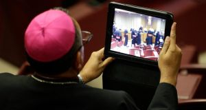 A bishop takes a picture with a tablet during a synod of bishops in Paul VI's hall at the Vatican . Photograph: Max Rossi/Reuters