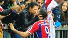 Robert Lewandowski  of Bayern Munich   kisses his wife Anna Stachurska after a game aganist Hannover 96 at the Allianz Arena in Munich. Keeping ticket prices low helps German clubs build a tight bond with the local community.  Photo:  Lennart Preiss/Bongarts/Getty