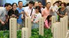 Customers look at a model of a new residential compound, at a showroom in Hangzhou, Zhejiang province. Photograph: Reuters