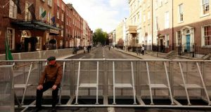 A man sits on barriers erected to keep demonstrators away from Leinster House during the announcement of the 2015 Budget