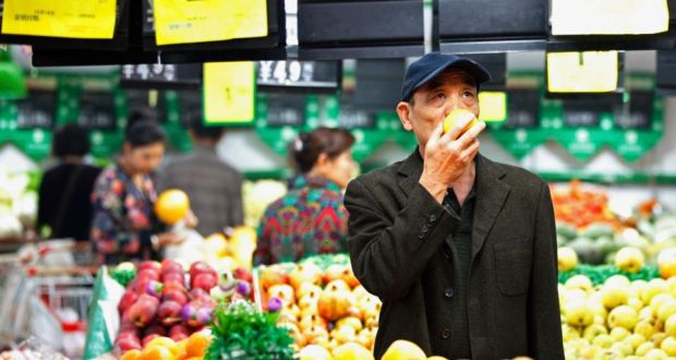 A customer selects fruits at a supermarket in Huaibei, Anhui province. China's inflation rate slowed more than expected in September to a near five-year low