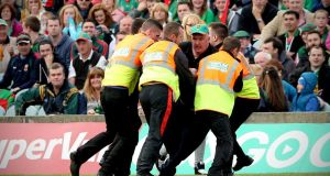 Mayo supporter Mick Barrett being removed from the pitch in the closing moments  of the Kerry-Limerick All-Ireland football semi-final in Limerick. Photograph: Inpho.