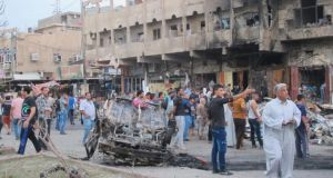 People gather at the site of a car bomb attack in Baghdad yesterday. The latest attacks follow a series of dramatic advances in Iraq by Islamic State fighters. Photograph: Reuters