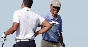 President Barack Obama with his Game Golf aid at Vineyard Golf Club. Photograph: AP Photo/Steven Senne