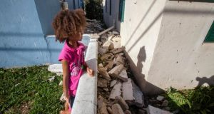 A girl views fallen pieces of a church roof after Hurricane Gonzalo passed through in Sandys Parish, western Bermuda. Photograph: Nicola Muirhead/Reuters