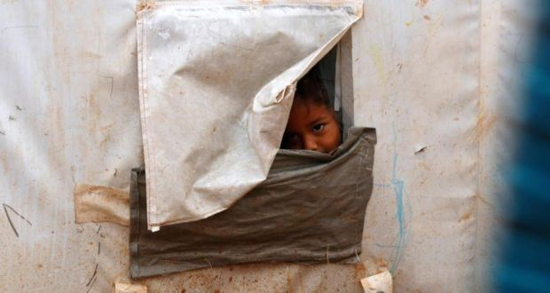 A child, internally displaced due to fighting between rebels and forces loyal to Syrian President Bashar al-Assad, looks out of his tent window in Ekda village refugee camp, beside the Syrian-Turkish border in northern Aleppo. Fierce fighting once again gripped the border town of Kobani overnight. Photograph: Reuters