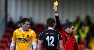 Kilcoo's Paul Devlin gets a yellow card from referee Noel Mooney during the Ulster club clash at Páirc Esler. Photo: Russell Pritchard/Presseye/Inpho