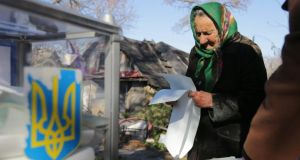 An elderly Ukrainian woman reads her ballot papers during the elections, in the Krenichi village, about 40km from Kiev. Photograph: Tatyana Zenkovich