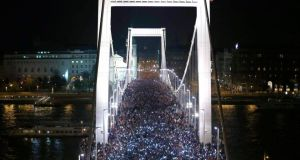 Tens of thousands of Hungarians hold up their mobile phones as they march across the Elisabeth Bridge during a protest against new tax on Internet data transfers in centre of Budapest. Photograph: Laszlo Balogh /Reuters