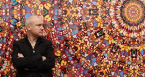 Damien Hirst in front of one of his works. Photograph: Oli Scarff/Getty Images
