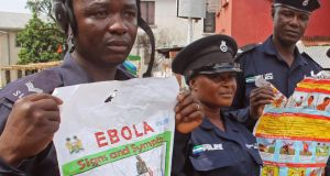Police officers hold up posters about Ebola in Freetown, Sierra Leone. Photograph: Youssouf Bah/AP