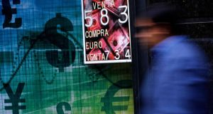 A pedestrian walks past a money exchange bureau with a board displaying the exchange rate of the US dollar