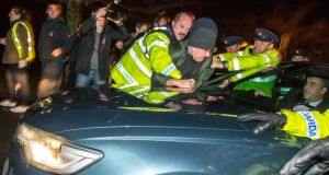 A small group of anti-water charges protesters surrounded the Taoiseach's car, kicking and banging it with placards, while one man who climbed on the bonnet had to be pulled away by gardaí.  Photo: James Connolly / PicSell