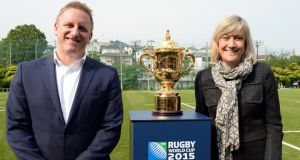 Debbie Jevans (R) and head of the Rugby World Cup Limited, Alan Gilpin (L) pose beside the Webb Ellis Cup, the winner's trophy for the upcoming England 2015 Rugby World Cup. Photograph: Toshifumi Kitamura/Getty Images