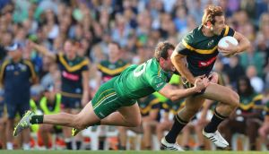 Australia's Jobe Watson looks to break free form the clutches of  Ireland captain Michael Murphy at Paterson Stadium in Perth. Photograph: Cathal Noonan / Inpho