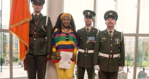 Esther Gaba  with members of  the Irish army after receiving her citizenship at UCC. Photograph: Michael Mac Sweeney/Provision