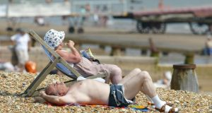 Beachgoers relax  on a  in Eastbourne in England during a heatwave. A new report warns that global warming could increase vulnerability to life-threatening heatwaves more than 10-fold in parts of Europe by the end of the century. Photograph: Phil Cole/Getty Images.