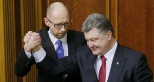 Ukraine's president Petro Poroshenko (right) congratulates newly-appointed prime minister Arseny Yatseniuk during a parliament session in Kiev on Thursday. Photograph: Reuters/Gleb Garanich