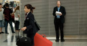 Author Alain de Botton (R) makes notes during his week as writer-in-residence at Heathrow Airport, west London, on August 20, 2009.