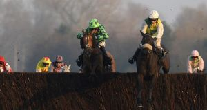 Leighton Aspell riding Many Clouds (right) clear at the last to win The Hennessy Gold Cup from Houblon Des Obeaux () at Newbury. Photograph: Alan Crowhurst/Getty Images